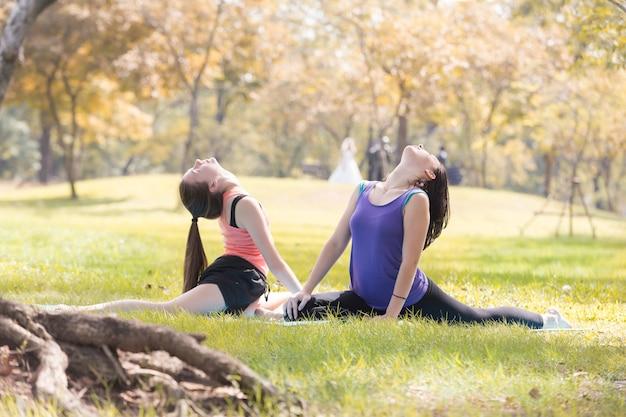 Feriado minhas irmãs que fazem a ioga da pose da ioga no conceito saudável do esporte do parque público.