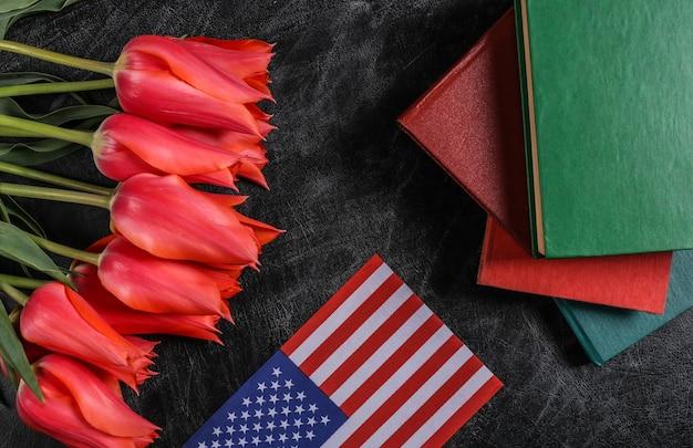 Feriado nacional. buquê de tulipas, livros e bandeira dos eua em um quadro de giz. de volta à escola. dia do conhecimento