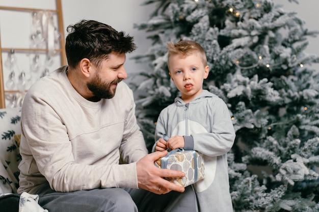 Feriado natal pai bonito brincando com filho pequeno bonito perto da árvore decorada do ano novo em casa pai de tradição familiar dá um presente para seu filho