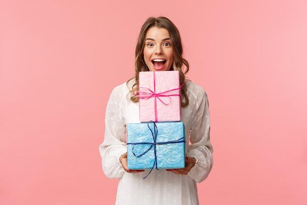 Feriados, celebração e conceito de mulheres. retrato de menina alegre feliz gosta de comemorar aniversário e receber presentes, segurando duas caixas de presente e sorrindo, em uma parede rosa