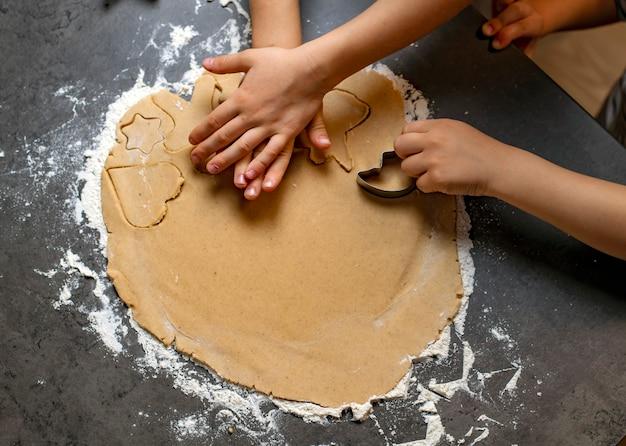 Feriados de natal e ano novo, mamãe e filhos preparam biscoitos de gengibre