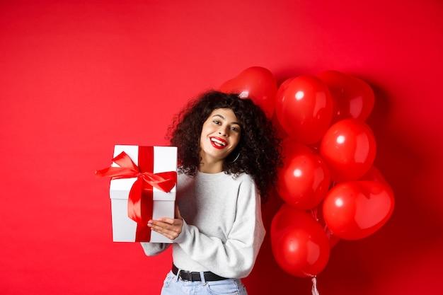 Feriados e comemorações. feliz aniversário menina segurando presente e posando perto de balões de festa de hélio, sorrindo animado, parede vermelha.