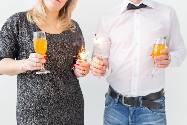 Feriados, natal, dia dos namorados e conceito de ano novo - mulher e homem celebram e segura vinho em um copo sobre fundo branco.