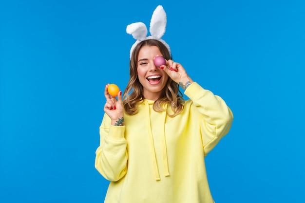 Feriados, tradições e celebração conceito feliz alegre jovem bonita fêmea comemorando o dia de páscoa, mostrando dois ovos pintados e rindo, usando orelhas de coelho bonito, azul