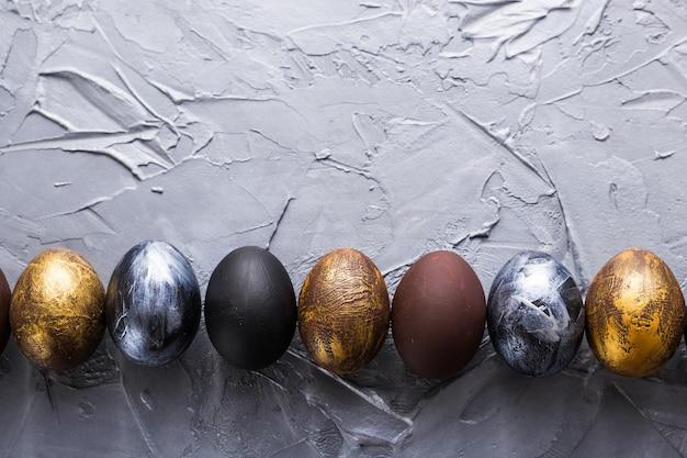 Feriados, tradições e conceito da páscoa - ovos da páscoa à moda escuros no fundo cinzento com copyspace.