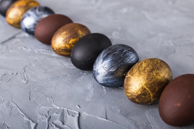 Feriados, tradições e conceito da páscoa - ovos da páscoa à moda escuros no fundo cinzento.