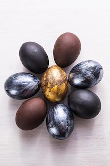 Feriados, tradições e conceito da páscoa - ovos da páscoa à moda escuros no fundo de madeira branco.
