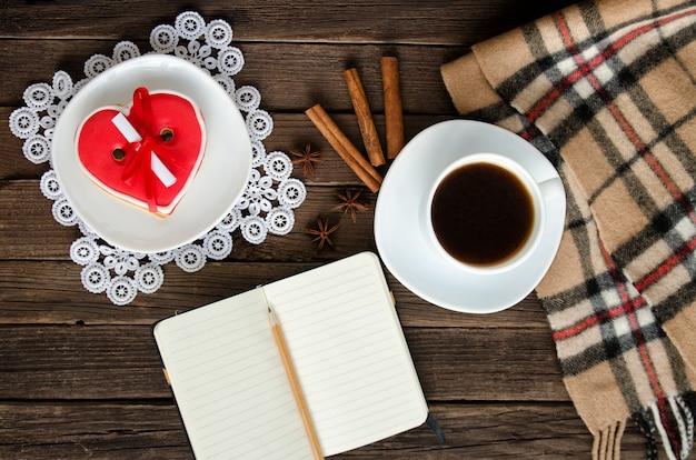 Férias aconchegantes. caneca de café, pão de mel em forma de coração, bloco de notas e lápis, xadrez e especiarias. vista do topo