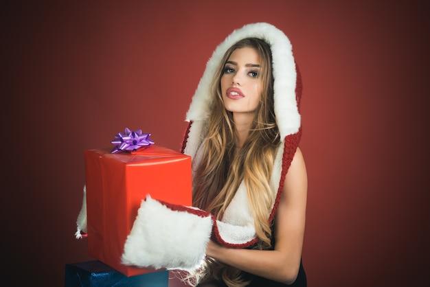 Férias, ano novo e natal, linda garota sexy com cabelo comprido usando chapéu de papai noel segura