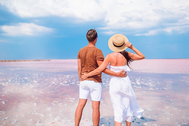 Férias com a família. jovem casal aproveita férias na praia com uma vista incrível do lago de sal rosa