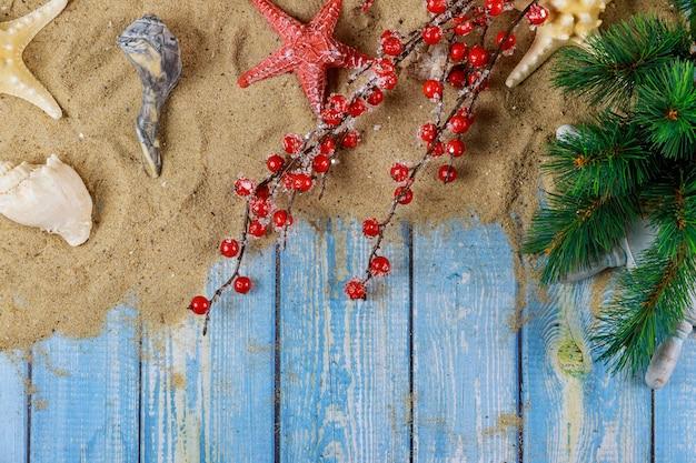 Férias de férias com conchas do mar de starfishand em um galho de árvore de natal com fundo azul de madeira