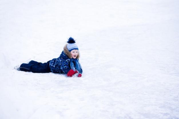 Férias de inverno ativo - menino bonitinho patinando em uma pista de gelo