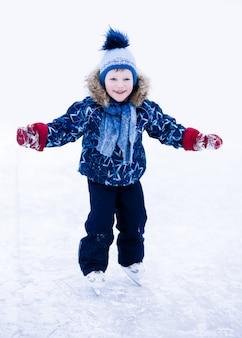 Férias de inverno ativo - menino bonitinho patinar onn pista de gelo