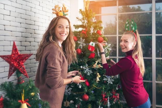 Férias de inverno, conceito de celebração e pessoas. mulher decorando árvore de natal com bola