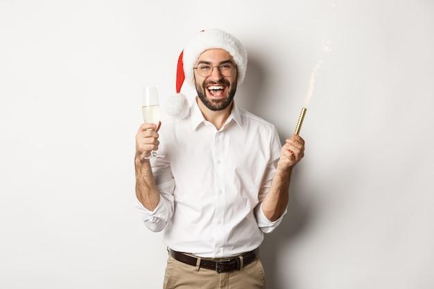 Férias de inverno e celebração. homem barbudo bonito na festa de ano novo, segurando fogo de artifício e champanhe, usando chapéu de papai noel
