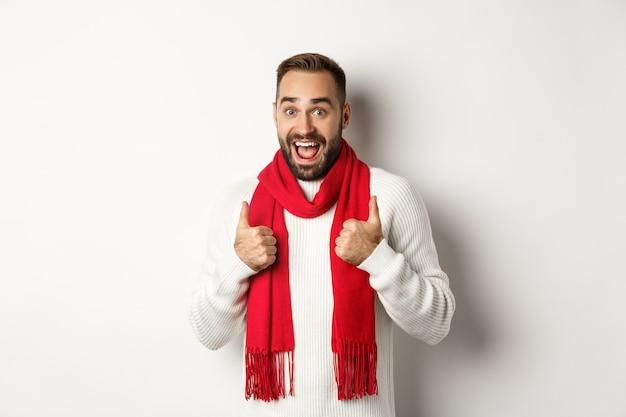 Férias de inverno e conceito de compras. homem barbudo alegre como tudo, mostrando os polegares em aprovação, surpreso contra um fundo branco