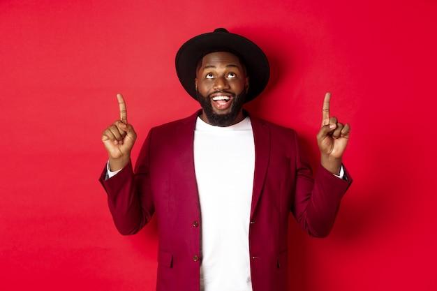 Férias de inverno e conceito de compras. homem negro alegre olhando e apontando os dedos para cima, conferindo a promoção de natal, em pé sobre um fundo vermelho.