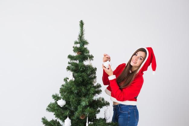 Férias de inverno e conceito de pessoas amando casal pendurando enfeites na árvore de natal no quarto branco