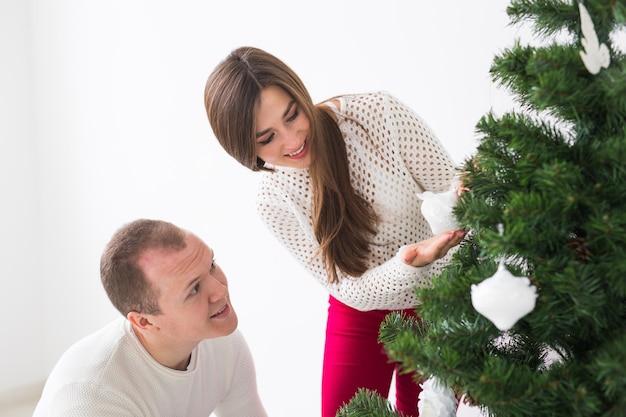 Férias de inverno e conceito de pessoas - casal apaixonado pendurando enfeites na árvore de natal