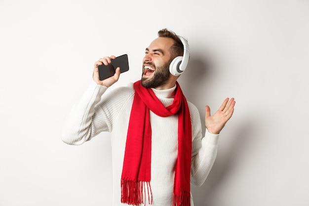Férias de inverno e conceito de tecnologia. homem tocando aplicativo de karaokê no celular, cantando no smartphone, usando fones de ouvido, em pé sobre um fundo branco