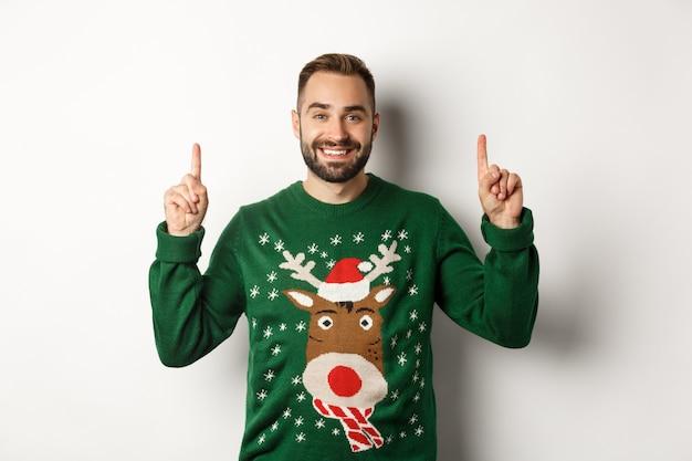 Férias de inverno e natal. bonito homem barbudo com suéter verde, apontando o dedo para cima e sorrindo, mostrando anúncio, fundo branco