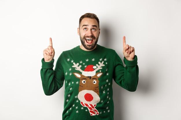Férias de inverno e natal. homem barbudo animado em suéter engraçado olhando, apontando os dedos para o espaço da cópia, em pé sobre um fundo branco.