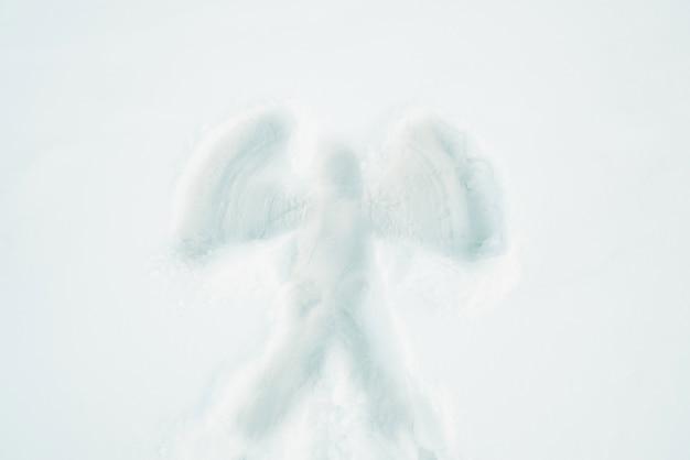 Férias de inverno e o conceito de natal. silhueta de anjo na vista superior da superfície de neve.