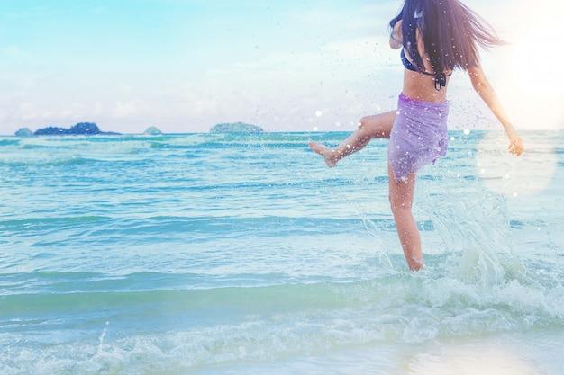 Férias de liberdade mulher sexy relaxar na praia brincando de salpicos de água
