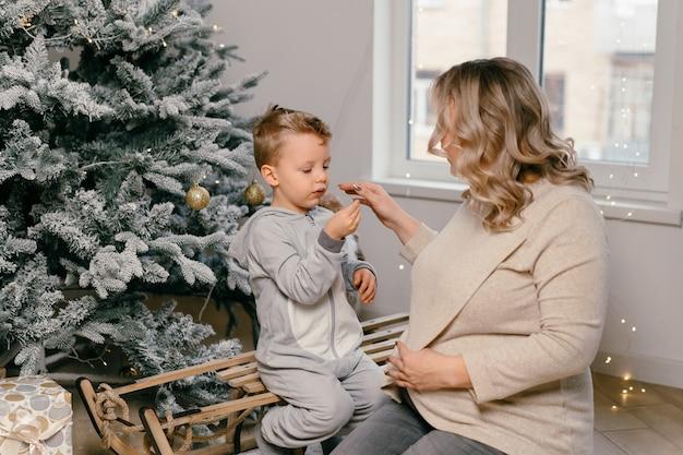 Férias de natal caucasiana mãe brincando com filho fofo perto da árvore decorada do ano novo em casa tradição familiar