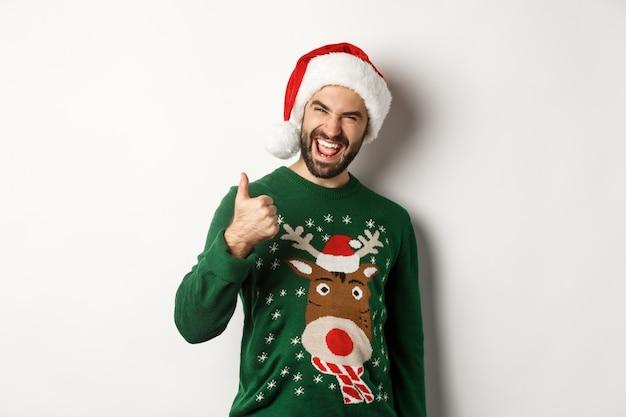 Férias de natal, celebração e conceito de festa. homem aproveitando o ano novo, aparecendo o polegar em aprovação, usando chapéu de papai noel, fundo branco.