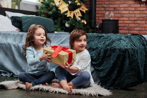 Férias de natal com presentes para essas duas crianças que estão sentadas dentro de casa no belo quarto perto da cama.