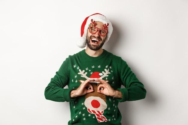 Férias de natal, conceito de celebração. cara feliz com chapéu de papai noel e óculos de festa, tirando sarro do suéter engraçado, em pé sobre um fundo branco