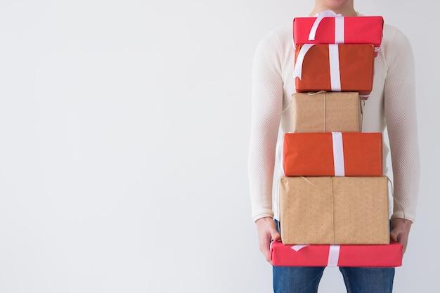 Férias de natal e presentes conceito close-up de um homem segurando um monte de presentes no fundo branco