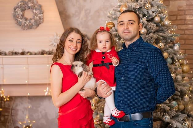 Férias de natal em família feliz. para a menina, o papai noel trouxe um coelho.