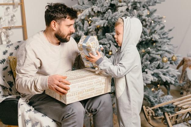 Férias de natal pai bonito brincando com o filho pequeno e bonito perto da árvore decorada do ano novo em casa menino de tradição familiar dá um presente para o pai