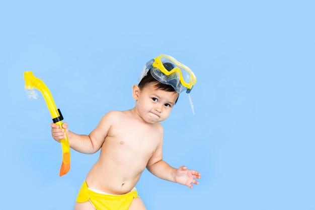 Férias de praia menino engraçado com tubo de máscara para nadar na água do mar