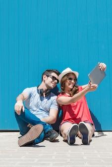 Férias de verão, adolescente e conceito de tecnologia - dois adolescentes sorridentes em óculos de sol tirando uma selfie com o tablet pc