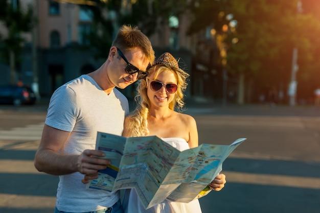 Férias de verão - casal sorridente com óculos escuros e mapa da cidade