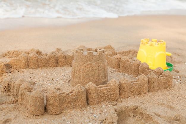 Férias de verão com castelo de areia na praia