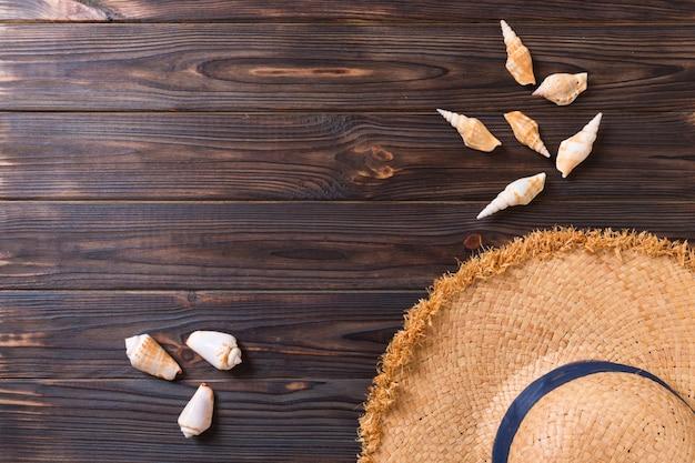 Férias de verão com chapéu de palha e conchas na madeira