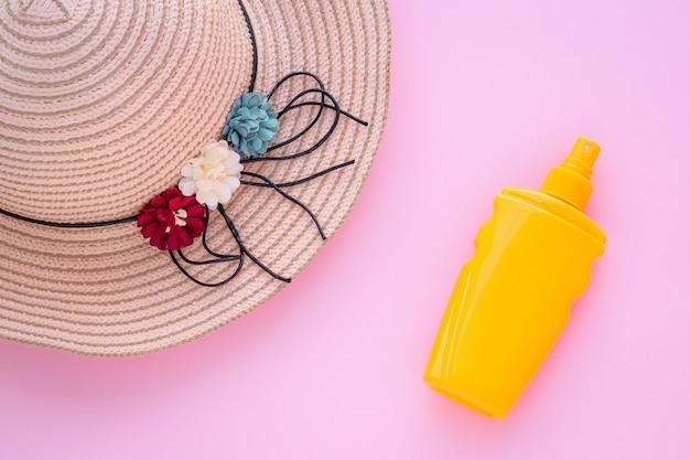 Férias de verão, conceito de proteção. chapéu de vime e protetor solar em garrafa.