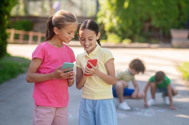 Férias de verão. duas garotas bonitas sorridentes de cabelos compridos em pé com smartphones e garotos agachados desenhando no asfalto atrás