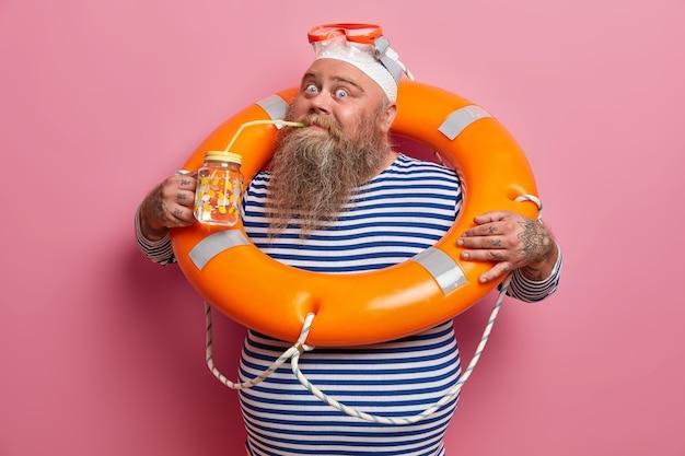 Férias de verão e conceito de recreação. homem adulto barbudo rechonchudo bebe água doce durante o dia quente, posa com bóia laranja de resgate, usa touca e óculos de proteção, isolados na parede rosa.