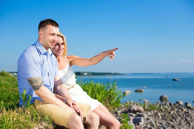 Férias de verão e conceito de viagens - casal feliz e sorridente apreciando a vista para o mar na praia rochosa