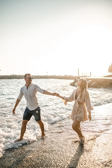 Férias de verão e viagens. mulher sexy e homem na água do mar ao pôr do sol. casal apaixonado relaxa na praia ao nascer do sol. relacionamento amoroso de um casal desfrutando de um dia de verão juntos. foco seletivo