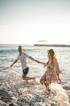 Férias de verão e viagens. mulher sexy e homem na água do mar ao pôr do sol. casal apaixonado relaxa na praia ao nascer do sol. relacionamento amoroso de um casal em um dia de verão juntos