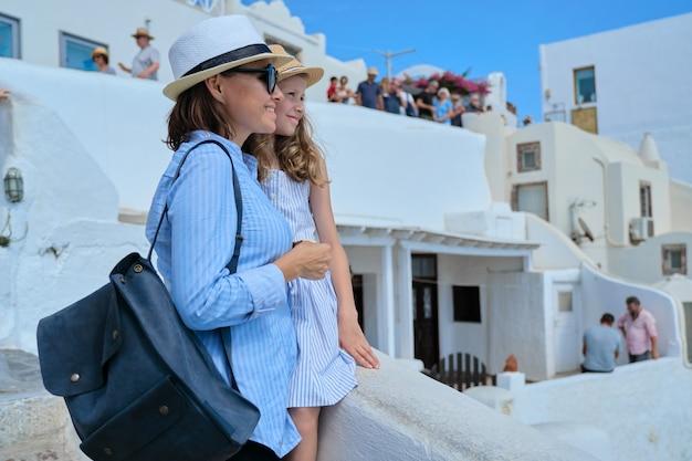 Férias de verão em cruzeiro no mar mediterrâneo na ilha grega de santorini, na vila de oia, mãe e filha viajam juntas