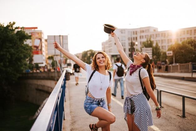 Férias de verão, feriados, festa, festival e conceito de pessoas. duas garotas dançando na ponte da cidade.