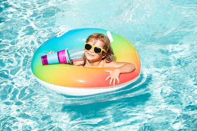 Férias de verão. garoto no parque aquático. criança beber coquetel na piscina.