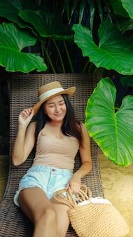 Férias de verão jovem asiático linda mulher relaxando na piscina de um resort spa lindo resort tropical em frente à praia com piscina